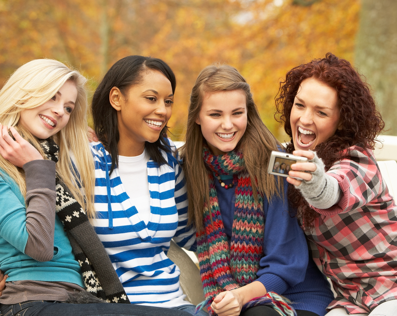 Four high school girls smile as they take a selfie with a camera in an autumn park. They are feeling more kind and inviting after group therapy for teen girls in west bloomfield, mi. Therapyology offers group therapy for teenagers in west bloomfield, mi, adolescent group therapy in west bloomfield, mi and more. Contact us today!