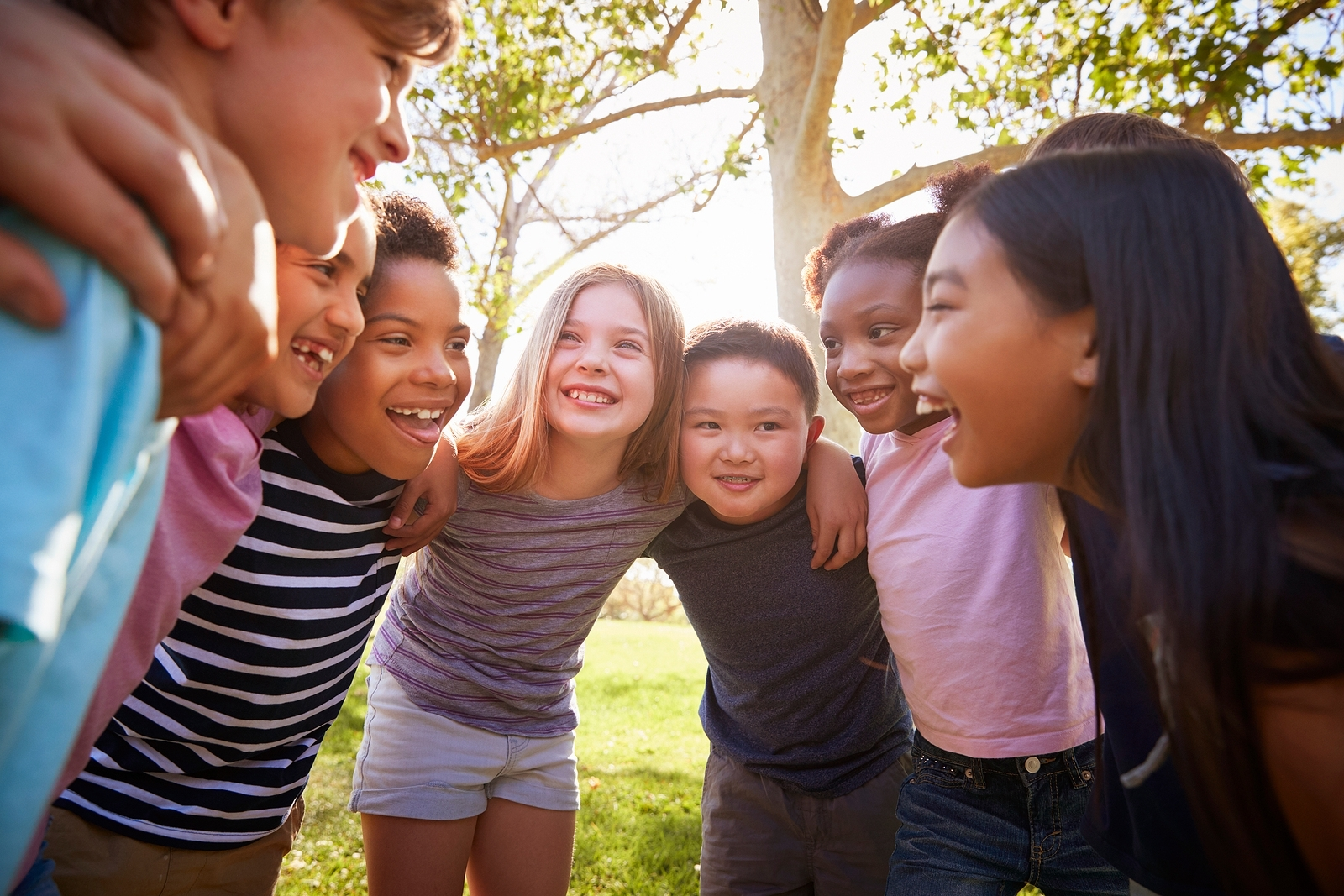 Group of children huddle as they smile at one another. They are part of Banana Splits, a children of divorce support group in West Bloomfield, MI. Therapyology offers therapy for children of divorce in West Bloomfield, MI. Contact us to get in touch with a child divorce therapist today.