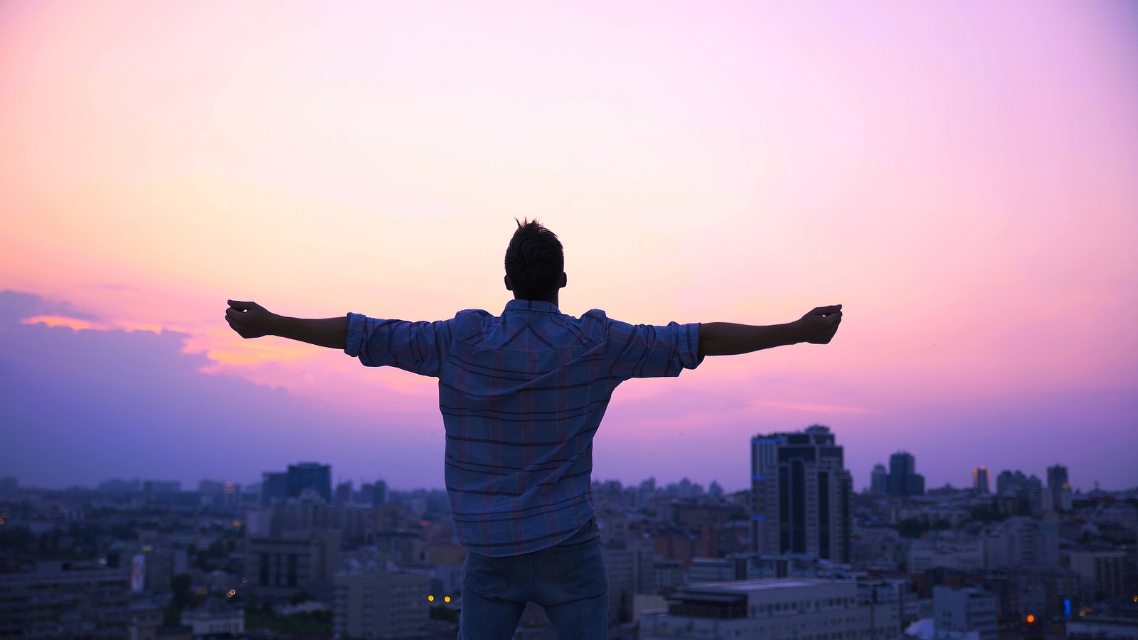 Man with arms outstretched stands on top of a building under the evening sky. He is happy that he has overcome his past trauma. Therapyology offers trauma therapy in West Bloomfield, MI, treatment for ptsd, and more. Contact us today to start trauma therapy in Michigan.