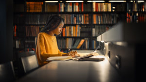 A student writes something while studying intently in a library. Life transitions counseling in Michigan can help you cope with college. Learn more about transitions counseling in West Bloomfield, MI today!